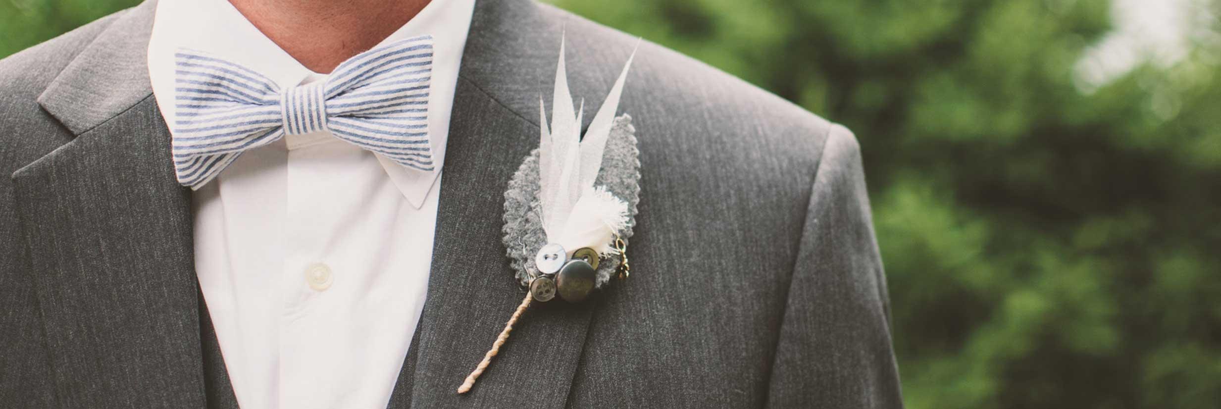 Męska przypinka do butonierki z białymi piórami.