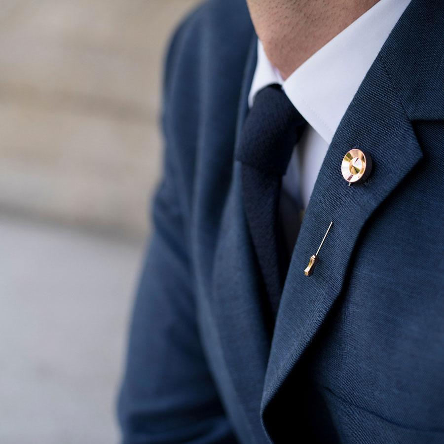 Ozdobna metalowa szpilka umieszczona w męskiej marynarce.